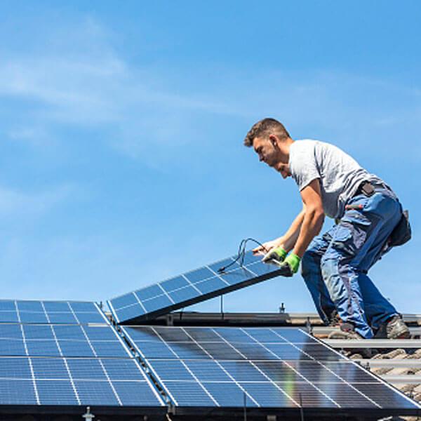 Elektriker montiert Photovoltaikanlage auf einem Dach