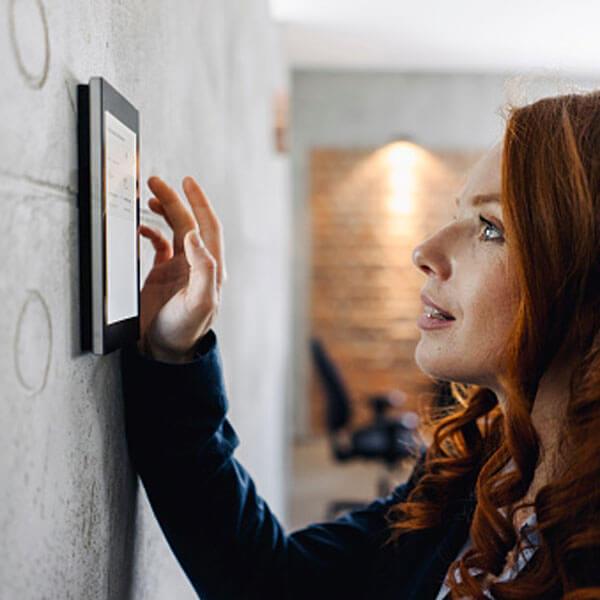 Frau bedient auf einem Touchpanel an der Wand die Beleuchtung im Raum